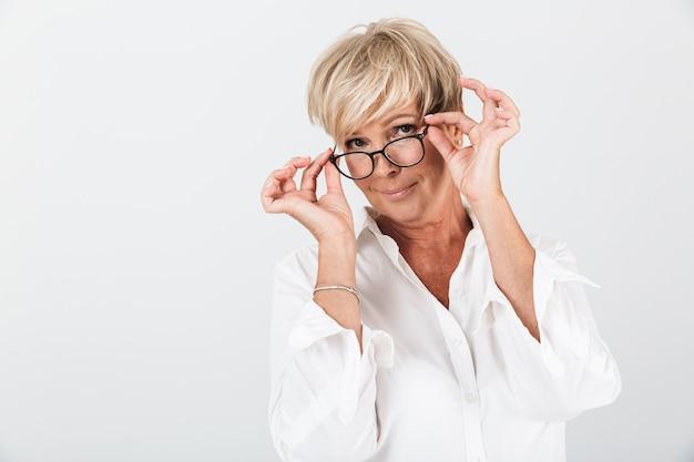 Portret van een verleidelijke volwassen vrouw die een bril vasthoudt en naar een camera kijkt die over een witte muur in de studio wordt geïsoleerd