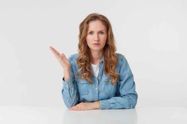 Portret van een verloren jonge vrouw met lang blond golvend haar, zittend aan tafel, een handpalm omhoog, kijkt sceptisch ontevreden en verontwaardigd, geïsoleerd op witte achtergrond.