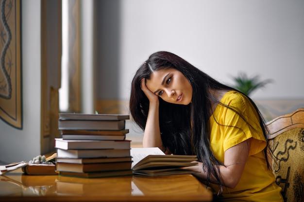 Portret van een vermoeid studentenmeisje dat met boeken bij de oude bibliotheek bestudeert