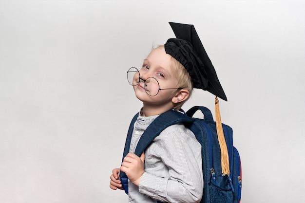 Portret van een vermoeide blonde jongen in glazen, een academische hoed en een schooltas