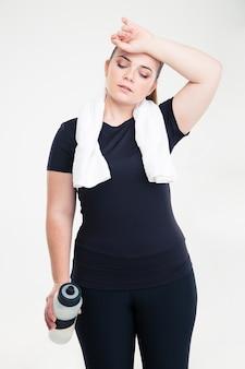 Portret van een vermoeide dikke vrouw in sportkleding die geïsoleerd op een witte muur staat