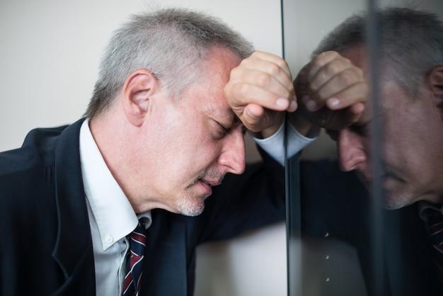 Portret van een vermoeide en beklemtoonde zakenman die tegen een glas ligt