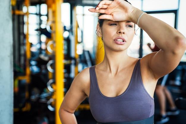 Portret van een vermoeide, fitte vrouw die rust heeft na een training in de sportschool