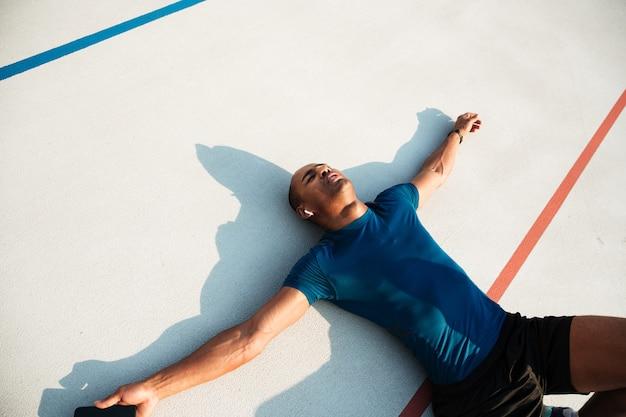 Portret van een vermoeide jonge afrikaanse fitness man in koptelefoon