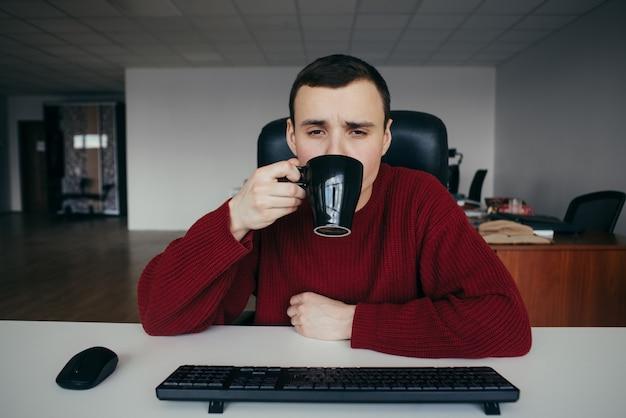 Portret van een vermoeide jonge kantoor werknemer koffie drinken op het werk. de situatie op kantoor