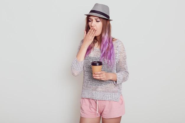 Portret van een vermoeide jonge vrouw die een hoed draagt, fel violet haar heeft, een wegwerpbeker met koffie vasthoudt, energie nodig heeft om wakker te worden, geïsoleerd over een grijze achtergrond.