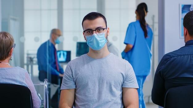 Portret van een vermoeide jongeman met gezichtsmasker tegen coronavirus in de wachtruimte van het ziekenhuis, kijkend naar de camera. senior man tijdens overleg in onderzoekskamer.