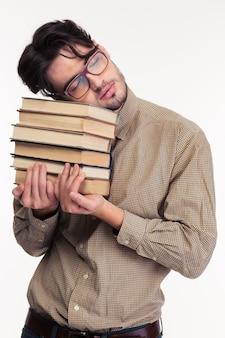 Portret van een vermoeide man die boeken vasthoudt en slaapt geïsoleerd op een witte muur