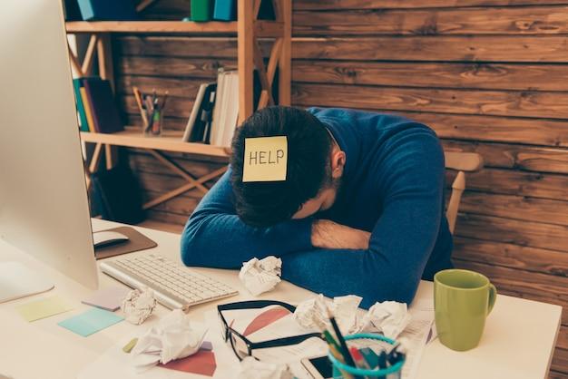 Portret van een vermoeide man die een lange werkdag heeft en hulp nodig heeft
