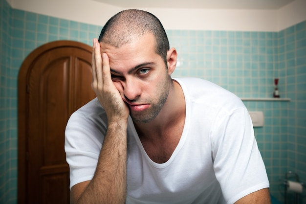 Portret van een vermoeide man in de spiegel in de badkamer kijken