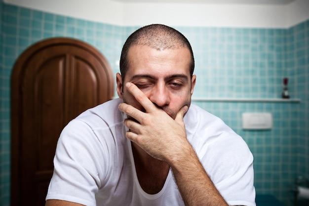 Portret van een vermoeide man in de spiegel in zijn badkamer kijken