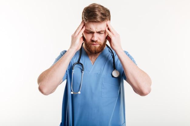 Portret van een vermoeide mannelijke dokter die aan een hoofdpijn lijdt
