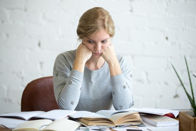 Portret van een vermoeide student vrouw aan het bureau