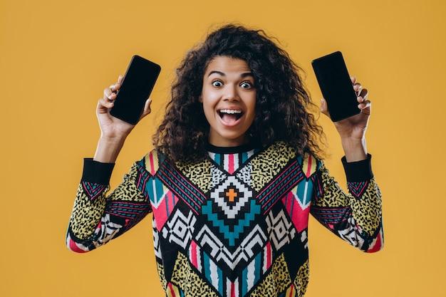 Portret van een verrast afro-amerikaanse vrouw in een veelkleurige trui, met twee smartphones in haar handen. kiezen, een telefoon kopen.