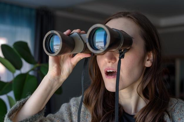 Portret van een verrast brunette met verrekijker kijkt uit het raam en bespioneert buren