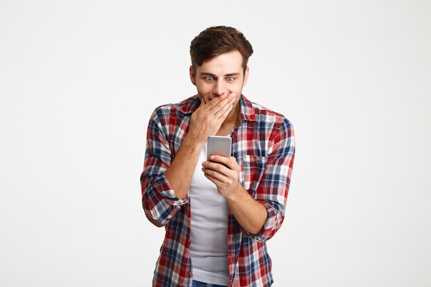 Portret van een verrast casual man kijken naar mobiele telefoon