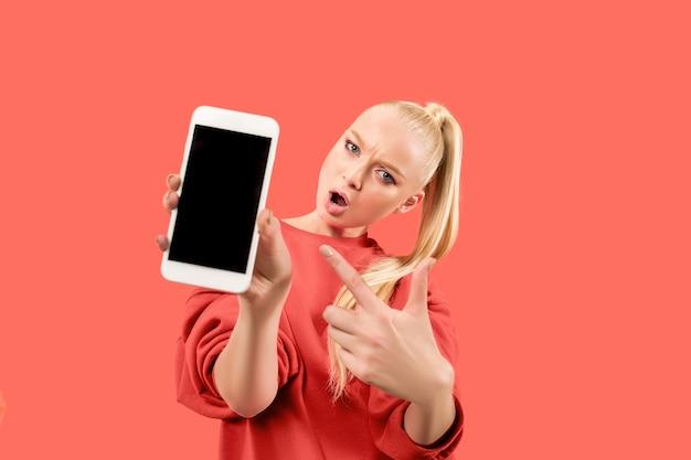 Portret van een verrast, glimlachend, gelukkig, verbaasd meisje dat een lege het scherm mobiele telefoon toont die over koraalachtergrond wordt geïsoleerd.