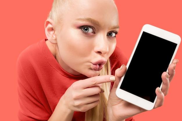 Portret van een verrast, glimlachend, gelukkig, verbaasd meisje dat een lege scherm mobiele telefoon toont die over koraalachtergrond wordt geïsoleerd.