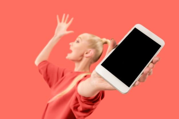 Portret van een verrast, glimlachend, gelukkig, verbaasd meisje dat een lege scherm mobiele telefoon toont