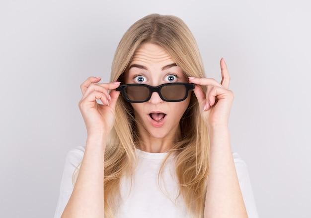 Portret van een verrast jong mooi meisje in brillen camera kijken terwijl opgewekt glazen. geïsoleerd over grijs