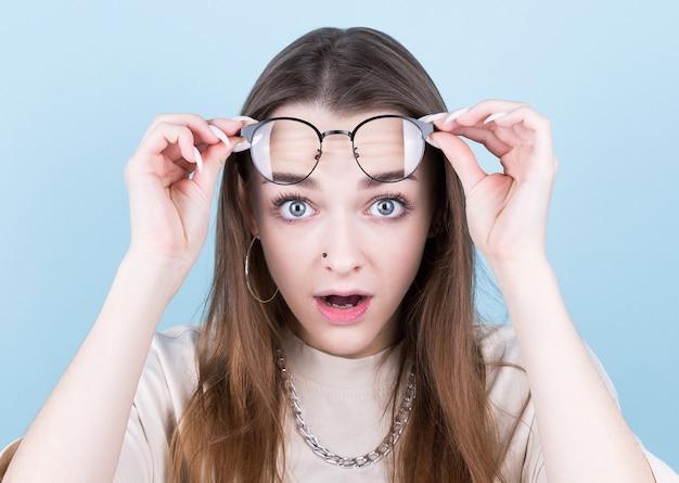 Portret van een verrast jong mooi meisje in brillen camera kijken terwijl opgewekt glazen. geïsoleerd over grijze achtergrond