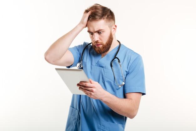 Portret van een verrast jonge arts in blauw uniform