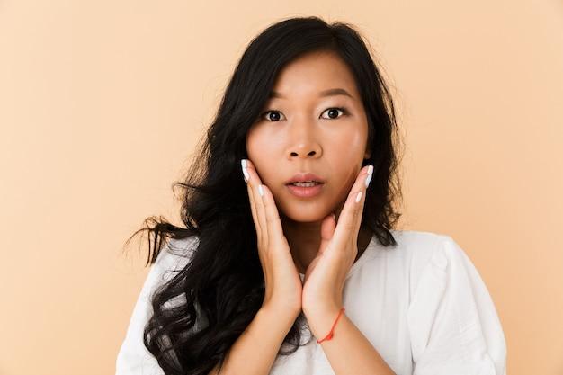Portret van een verrast jonge aziatische vrouw