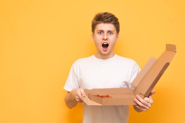 Portret van een verrast jongen met een doos pizza in zijn handen
