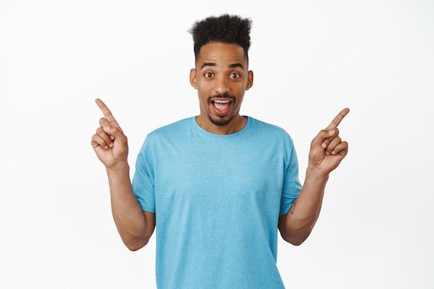 Portret van een verraste afro-amerikaanse man die met de vingers zijwaarts wijst, links en rechts producten toont, twee verkoopkortingen, staande in blauw t-shirt op wit.