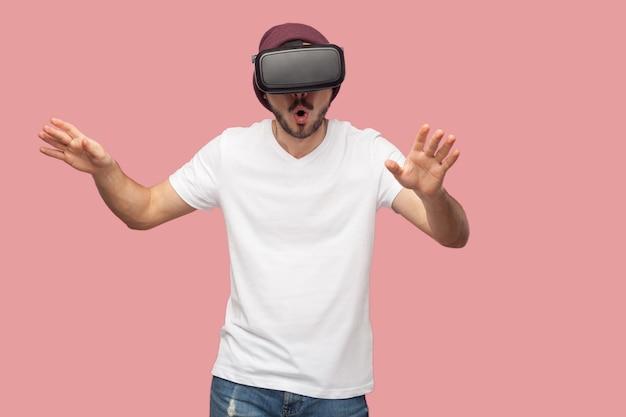 Portret van een verraste, bebaarde jonge hipster-man in een wit overhemd en een casual hoed die staat, vr draagt en video kijkt op de simulator met opgeheven armen. binnen, geïsoleerd, studio-opname, roze achtergrond