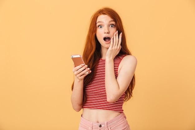 Portret van een verraste emotionele schattige jonge mooie roodharige vrouw die zich geïsoleerd over een gele muur stelt met behulp van chatten op de mobiele telefoon
