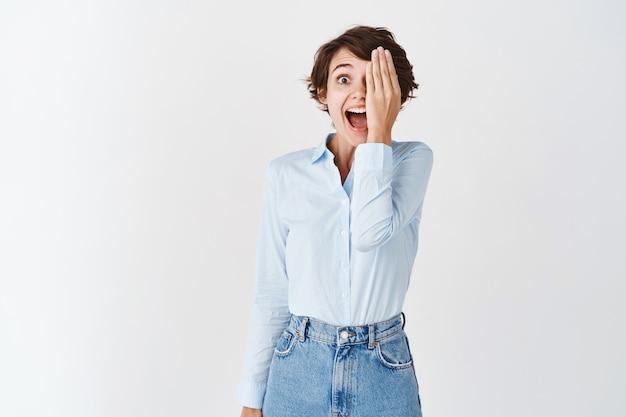 Portret van een verraste en gelukkige vrouw bedekt de helft van het gezicht met de hand en schreeuwt van vreugde en verbazing, kijkt naar iets cools, staat op een witte muur