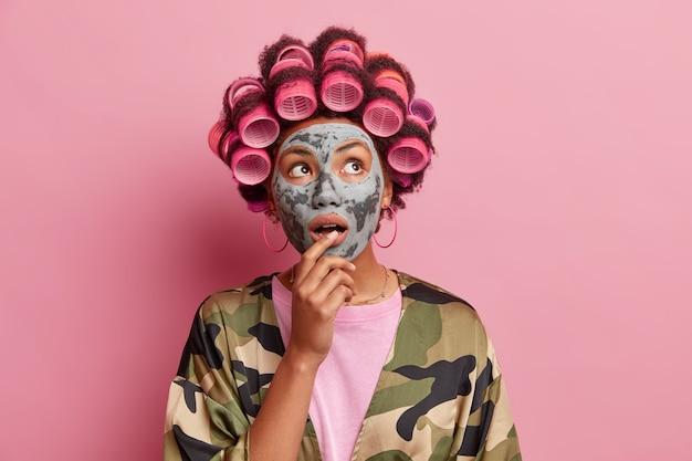 Portret van een verraste huisvrouw past een kleimasker op het gezicht toe, kijkt verbaasd hierboven, maakt een kapsel met haarrollers en draagt een huisgewaad tegen een roze muur. schoonheidsprocedures thuis.