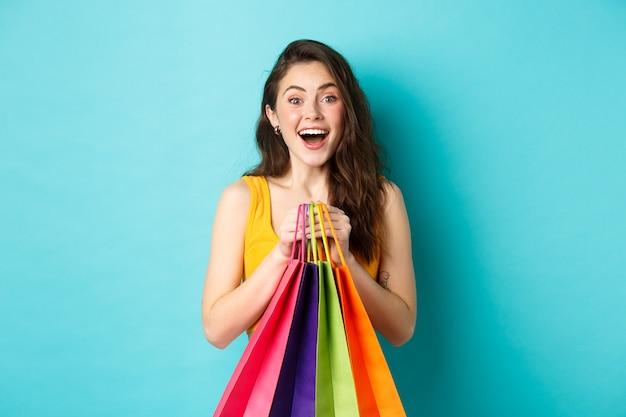 Portret van een verraste jonge vrouw die verbaasd naar de camera kijkt, boodschappentassen vasthoudt, kortingen in de winkel ziet, over een blauwe achtergrond staat