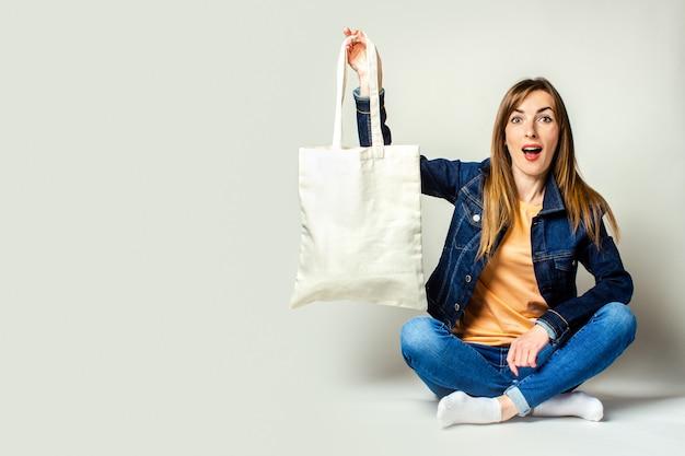 Portret van een verraste jonge vrouw zitten met gekruiste benen, met een linnen tas met aankopen op een lichte achtergrond