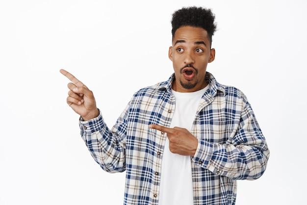 Portret van een verraste jonge zwarte man die wijst, met ontzag naar links kijkt, verbaasd staart naar iets cools, reclame opzij bekijkt, in vrijetijdskleding op wit staat