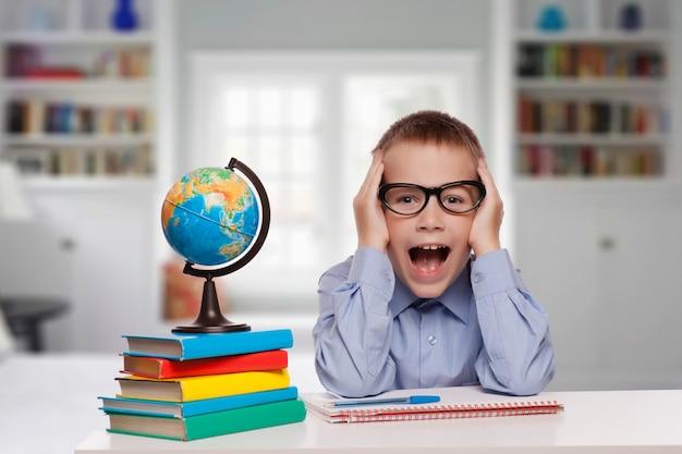 Portret van een verraste kleine jongen in een bril en pak. geïsoleerd op witte achtergrond.