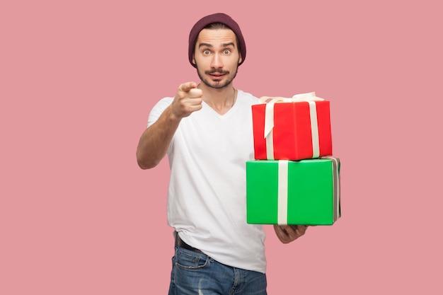Portret van een verraste knappe bebaarde jonge hipster man in wit overhemd en casual hoed staande, met twee huidige doos, wijzende vinger naar camera. binnen, geïsoleerd, studio-opname, roze achtergrond