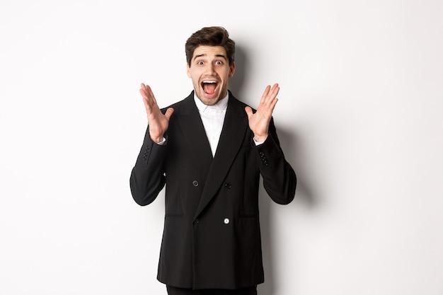 Portret van een verraste knappe zakenman in pak, reagerend op vakantiepromo, verbaasd naar de camera kijkend, staande op een witte achtergrond.