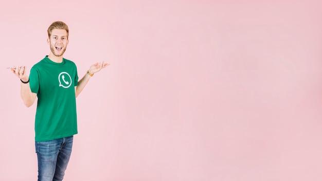 Portret van een verraste man met smartphone op roze achtergrond