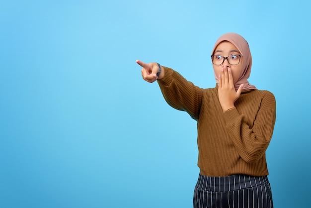 Portret van een verraste mooie aziatische vrouw die met de vinger wijst om ruimte op een blauwe achtergrond te kopiëren