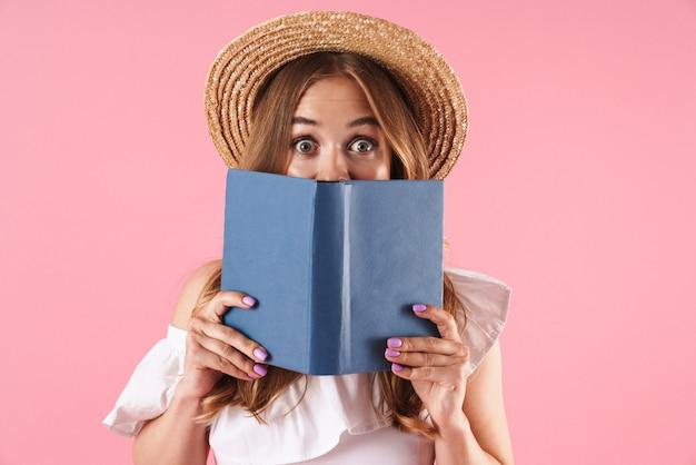 Portret van een verraste schattige jonge mooie vrouw die zich voordeed over een roze muur met een boek dat haar gezicht bedekt.