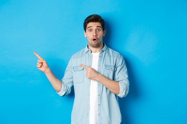 Portret van een verraste volwassen man in vrijetijdskleding die aankondiging toont, met de vingers naar links wijst en verbaasd kijkt, staande tegen een blauwe achtergrond