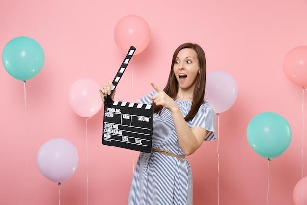 Portret van een verraste vrouw die de wijsvinger opzij wijst met klassieke zwarte film die filmklapper maakt op een roze achtergrond met kleurrijke luchtballonnen. verjaardagsfeestje, oprechte emoties van mensen.