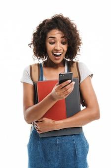 Portret van een verraste vrouw die een rugzak draagt met oefenboeken en een mobiele telefoon die over een witte muur wordt geïsoleerd