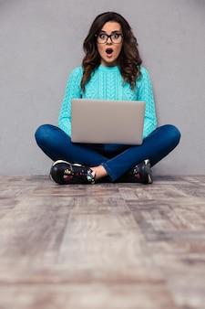 Portret van een verraste vrouw die op de vloer zit met een laptop en op een grijze muur