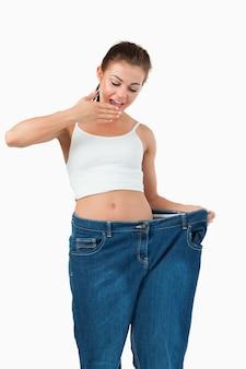 Portret van een verraste vrouw die te grote jeans draagt Premium Foto