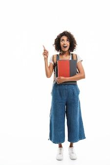 Portret van een verraste vrouw met een rugzak die met de vinger wijst naar copyspace en boeken vasthoudt die over een witte muur zijn geïsoleerd