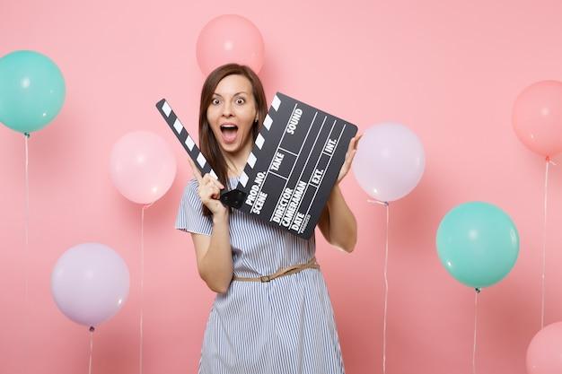 Portret van een verraste vrouw met geopende mond in blauwe jurk met klassieke zwarte film filmklapper op roze achtergrond met kleurrijke luchtballonnen. verjaardag vakantie feest mensen oprechte emoties.