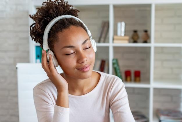 Portret van een verrukkelijk mulatmeisje met gesloten ogen in oortelefoons die aan muziek luisteren